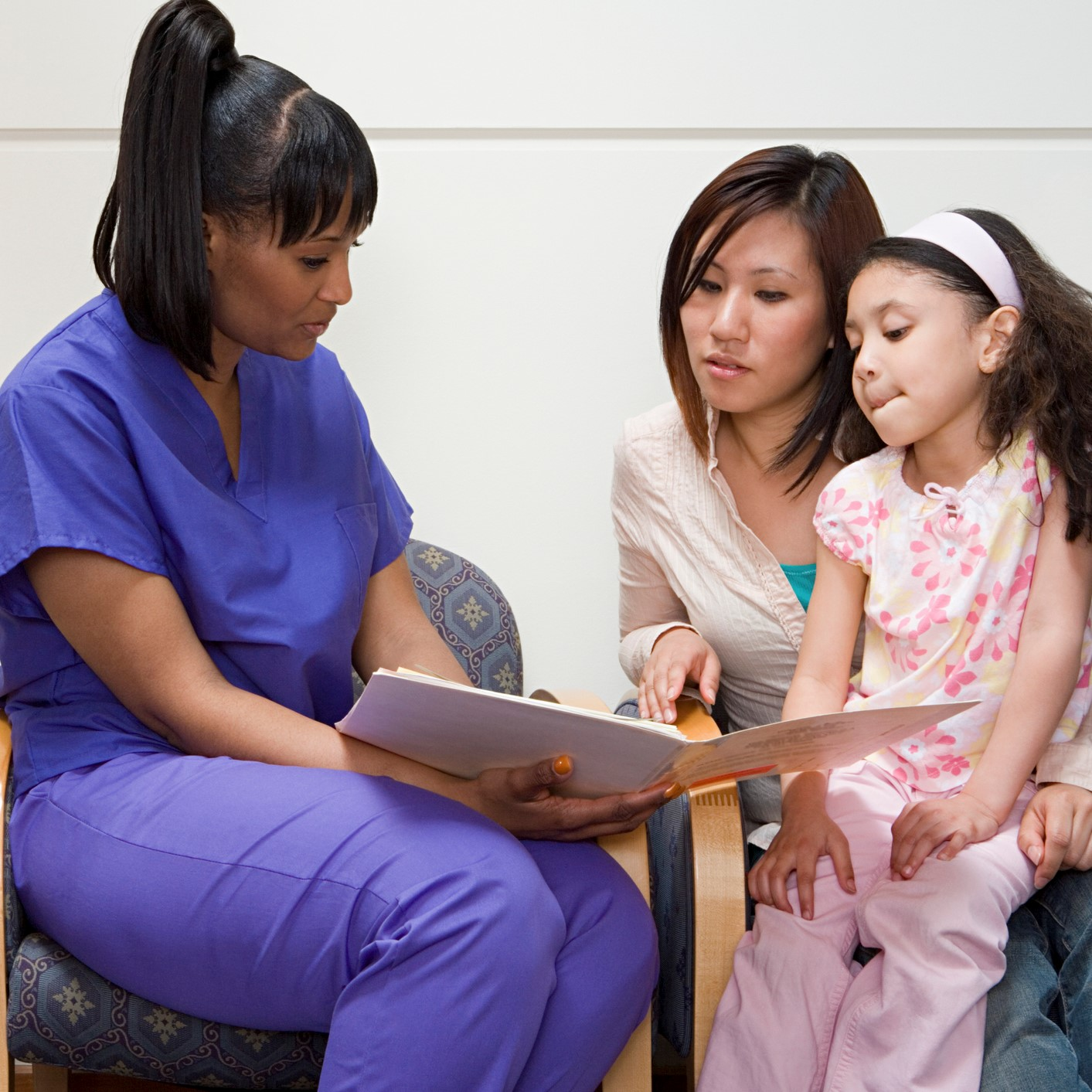 Nurse talking to mother and daughter