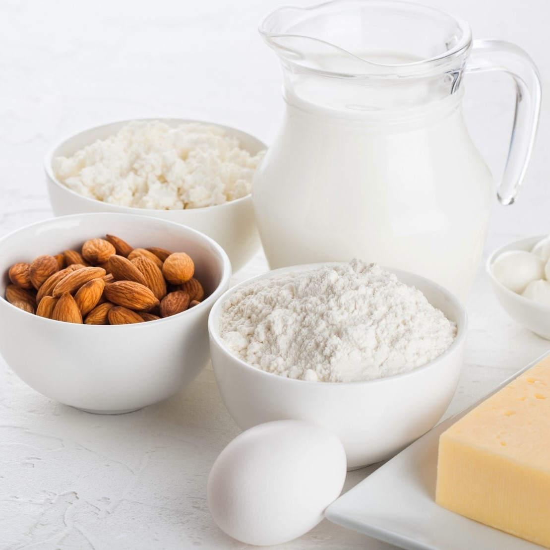 Glass jar of milk, bowl of cottage cheese, baking flour, almond, and eggs on table.