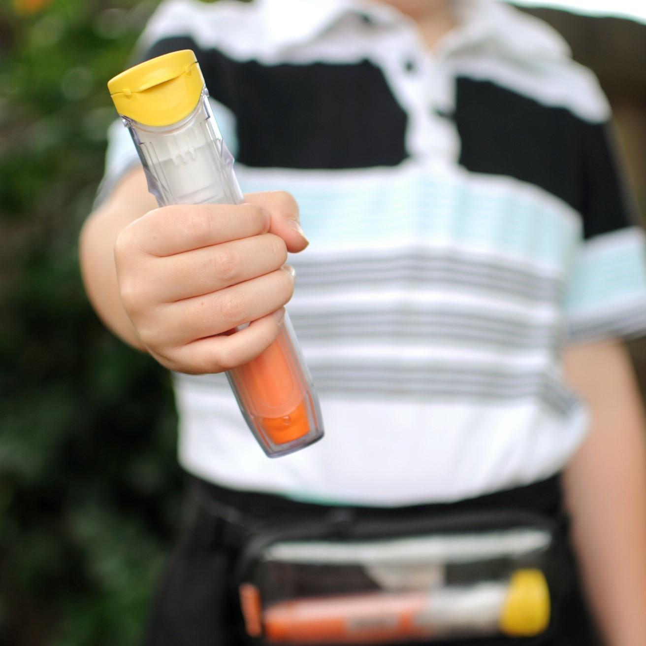 Child holding an epinephrine auto-injector, with another one shown in a small pouch around the child's waist.