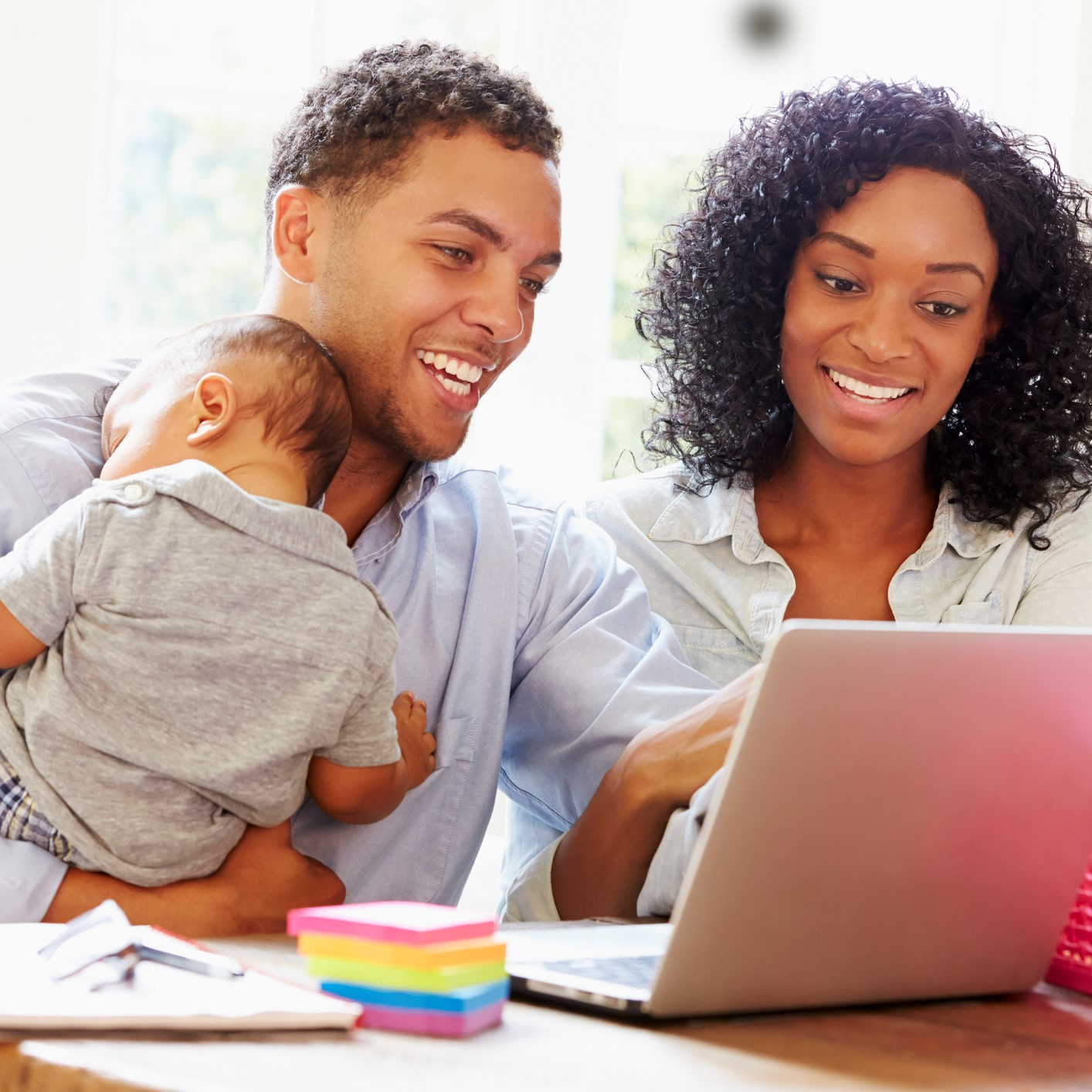Parents on laptop while dad is holding baby